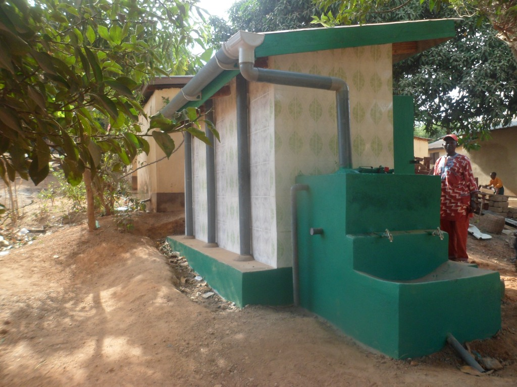 Amputee camp chairman inspecting newly constructed school latrine